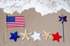 Американский флаг с морскими звёздами на песчаном пляже Стоковая Фотография RF