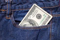 100 американских долларов счета в карманн голубых джинсов Стоковое фото RF