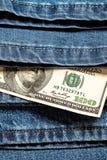 100 американских долларов на предпосылке джинсов Стоковая Фотография RF