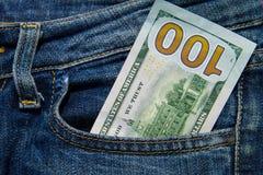 100 американских долларов счета в карманн голубых джинсов Стоковые Изображения