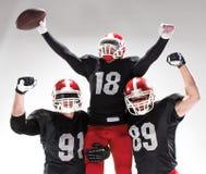 3 американских футболиста представляя на белой предпосылке Стоковая Фотография