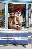 Амритсар, Индия, 5-ое сентября 2010: Молодой индийский человек, водитель грузовика, сидя и усмехаясь в его тележке Индия Стоковое Фото