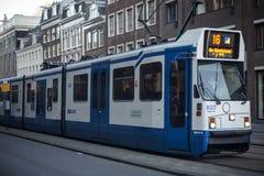 АМСТЕРДАМ, ГОЛЛАНДИЯ - 13-ОЕ МАЯ: Трамвай бежать в центре города среди пешеходов Стоковые Фотографии RF