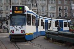 АМСТЕРДАМ, ГОЛЛАНДИЯ - 13-ОЕ МАЯ: Трамвай бежать в центре города среди пешеходов Стоковая Фотография