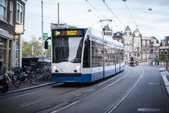 АМСТЕРДАМ, ГОЛЛАНДИЯ - 13-ОЕ МАЯ: Трамвай бежать в центре города среди пешеходов Стоковое фото RF