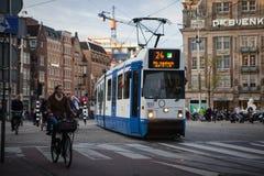 АМСТЕРДАМ, ГОЛЛАНДИЯ - 13-ОЕ МАЯ: Трамвай бежать в центре города среди пешеходов Стоковая Фотография RF