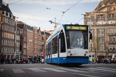 АМСТЕРДАМ, ГОЛЛАНДИЯ - 13-ОЕ МАЯ: Трамвай бежать в центре города среди пешеходов Стоковое Изображение