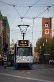 АМСТЕРДАМ, ГОЛЛАНДИЯ - 13-ОЕ МАЯ: Трамвай бежать в центре города среди пешеходов Стоковое Фото