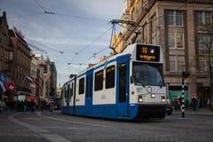 АМСТЕРДАМ, ГОЛЛАНДИЯ - 13-ОЕ МАЯ: Трамвай бежать в центре города среди пешеходов Стоковое Изображение RF