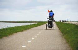 АМСТЕРДАМ, НИДЕРЛАНДЫ, апрель 2017: Человек на велосипеде вытягивая тележку младенца для колесницы велосипеда Туле Путь велосипед Стоковое фото RF
