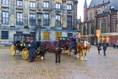 Амстердам, Нидерланды - 14-ое декабря 2017: Взгляд экипажа с лошадями и историческими зданиями в Амстердаме Стоковые Фото