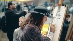 АМСТЕРДАМ, НИДЕРЛАНДЫ - 26-ОЕ ДЕКАБРЯ 2017 Красивая молодая женщина рисуя автопортрет Состязание искусства дилетанта сток-видео
