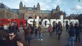 АМСТЕРДАМ, НИДЕРЛАНДЫ - 26-ОЕ ДЕКАБРЯ 2017 Туристов знак около Rijksmuseum, голландский соотечественник близко i Амстердам акции видеоматериалы