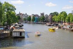 АМСТЕРДАМ, НИДЕРЛАНДЫ - 10-ОЕ ИЮНЯ 2010: Каналы Амстердама Амстердам столица и большинств многолюдный город Нидерландов Стоковые Фото