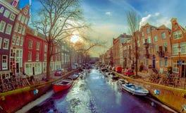 АМСТЕРДАМ, НИДЕРЛАНДЫ, 10-ОЕ МАРТА 2018: Взгляд домов и шлюпок на канале Амстердама Фото утра покрашенных домов внутри Стоковое Фото