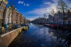 АМСТЕРДАМ, НИДЕРЛАНДЫ, 10-ОЕ МАРТА 2018: Внешний взгляд домов и шлюпок на канале Амстердама Фото утра покрашенный Стоковая Фотография RF