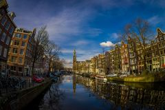АМСТЕРДАМ, НИДЕРЛАНДЫ, 10-ОЕ МАРТА 2018: Внешний взгляд домов и шлюпок на канале Амстердама Фото утра покрашенный Стоковое Изображение RF