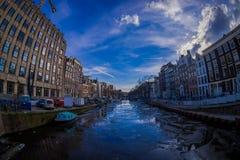 АМСТЕРДАМ, НИДЕРЛАНДЫ, 10-ОЕ МАРТА 2018: Дома и шлюпки на канале Амстердама Фото утра покрашенных домов в Стоковые Изображения RF