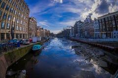 АМСТЕРДАМ, НИДЕРЛАНДЫ, 10-ОЕ МАРТА 2018: Дома и шлюпки на канале Амстердама Фото утра покрашенных домов в Стоковое Изображение