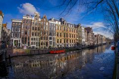 АМСТЕРДАМ, НИДЕРЛАНДЫ, 10-ОЕ МАРТА 2018: Дома и шлюпки на канале Амстердама Фото утра покрашенных домов в Стоковая Фотография RF