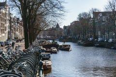 АМСТЕРДАМ, НИДЕРЛАНДЫ - 20-ое марта 2018: Канал и улица Амстердама Стоковые Фото