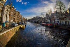 АМСТЕРДАМ, НИДЕРЛАНДЫ, 10-ОЕ МАРТА 2018: Красивый внешний взгляд домов и шлюпок на канале Амстердама Фото утра  Стоковое Изображение RF