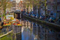 АМСТЕРДАМ, НИДЕРЛАНДЫ, 10-ОЕ МАРТА 2018: Красивый внешний взгляд домов и шлюпок на канале Амстердама с замороженным рекой Стоковые Фото