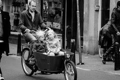 АМСТЕРДАМ, НИДЕРЛАНДЫ - 9-ОЕ МАЯ: Отец при 2 дет ехать велосипеды Стоковое Изображение