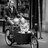 АМСТЕРДАМ, НИДЕРЛАНДЫ - 9-ОЕ МАЯ: Отец при 2 дет ехать велосипеды Стоковые Фото