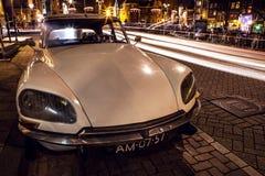 АМСТЕРДАМ, НИДЕРЛАНДЫ - 5-ОЕ ЯНВАРЯ 2016: Винтажный белый автомобиль припарковал в центре Амстердама на nighttime 5-ое января 201 Стоковые Изображения RF