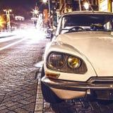 АМСТЕРДАМ, НИДЕРЛАНДЫ - 5-ОЕ ЯНВАРЯ 2016: Винтажный белый автомобиль припарковал в центре Амстердама на nighttime 5-ое января 201 Стоковая Фотография