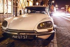 АМСТЕРДАМ, НИДЕРЛАНДЫ - 5-ОЕ ЯНВАРЯ 2016: Винтажный белый автомобиль припарковал в центре Амстердама на nighttime 5-ое января 201 Стоковое фото RF