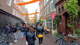 Амстердам, Нидерланд - 27-ое апреля 2019: Видео быстрого движения с людьми идя в улицы голландского Амстердама на День 201 короля акции видеоматериалы
