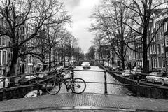 Амстердам, Нидерланд - 26-ое февраля 2010: Велосипед на улице около канала воды Велосипед очень популярный переход внутри стоковые фото