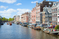 АМСТЕРДАМ 27-ОЕ АПРЕЛЯ: Городской пейзаж Амстердама с шлюпками вдоль банка канала на День короля, на 27,2015 -го апреля Стоковые Изображения