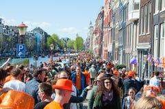 АМСТЕРДАМ 27-ОЕ АПРЕЛЯ: Locals и туристы празднуют День короля вдоль банка канала Singel на 27,2015 -го апреля, Нидерланды Стоковые Изображения RF