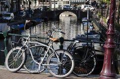 Амстердам нидерландская Голландия Европа 2 велосипеда на мосте Стоковые Фото