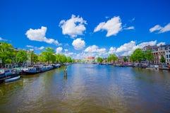 Амстердам, Нидерланды - 10-ое июля 2015: Большой водяной канал бежать через город с несколькими шлюпок припарковал наряду Стоковая Фотография RF