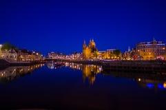 Амстердам, Нидерланды - 10-ое июля 2015: Водяные каналы ночой, красивым синим небом и светами города на обеих сторонах Стоковое фото RF