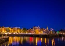 Амстердам, Нидерланды - 10-ое июля 2015: Водяные каналы ночой, красивым синим небом и светами города на обеих сторонах Стоковая Фотография RF
