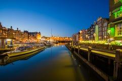 Амстердам, Нидерланды - 10-ое июля 2015: Водяные каналы ночой, красивым синим небом и светами города на обеих сторонах Стоковые Изображения RF