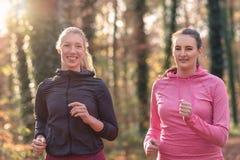 2 дамы привлекательных пригонки молодых вне jogging Стоковые Фотографии RF