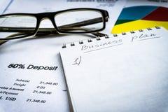 Анализирующ бизнес-план на столе - офис, финансовая концепция со стеклами стоковое фото rf
