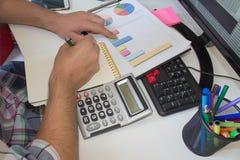 анализирующ чалькулятор подсчитывая данные финансовохозяйственные Рассчитывать калькулятор Рука на калькуляторе Стоковое фото RF