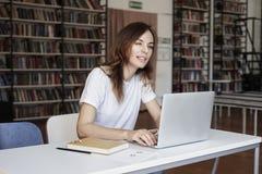 Аналитик волос молодой женщины длинный работая на со-работая офисе на запачканной компьтер-книжке, книжных полках позади, Коммерс стоковые фотографии rf