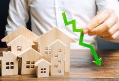 Аналитик держит вниз стрелку около деревянных домов Концепция падая рынка недвижимости Низкие цены и цена снабжения жилищем Умень стоковое фото