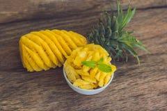 Ананас и куски ананаса на старой деревянной предпосылке Стоковое Изображение