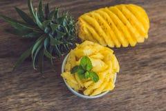 Ананас и куски ананаса на старой деревянной предпосылке Стоковые Фото