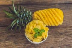 Ананас и куски ананаса на старой деревянной предпосылке Стоковое Изображение RF