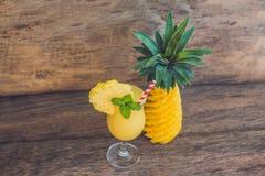 Ананас и smoothies ананаса на старой деревянной предпосылке Стоковая Фотография